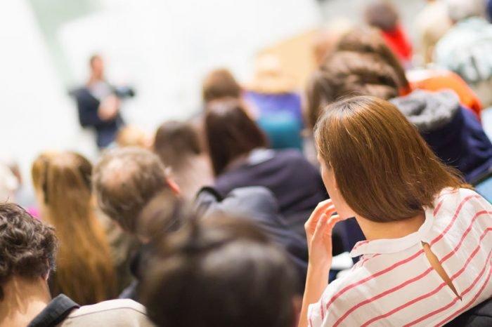 nainen kuuntelee seminaariluentoa