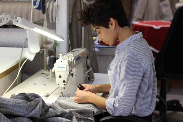 nainen ompelee vaatetta ompelukoneella