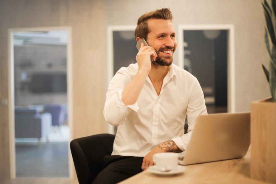 mies puhuu puhelimessa työpöydän ääressä
