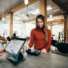 nainen maksaa ostoksia myymälässä