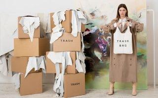 nainen poseeraa pahvilaatikoiden ja laukkumateriaalin keskellä