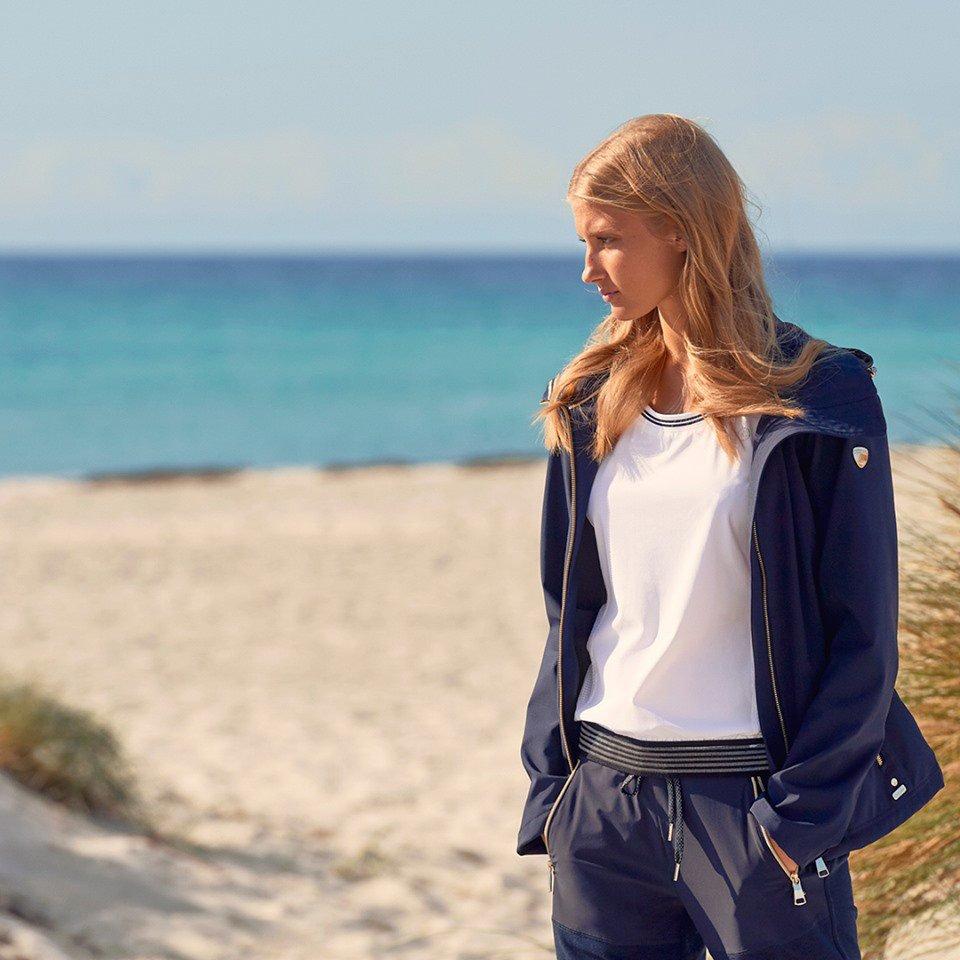 nainen poseeraa luhdan kampanjakuvassa rannalla
