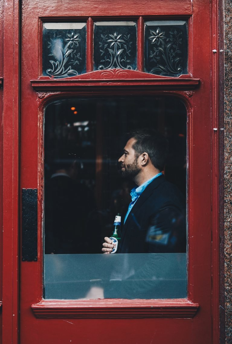 mies poseeraa juomapullon kanssa